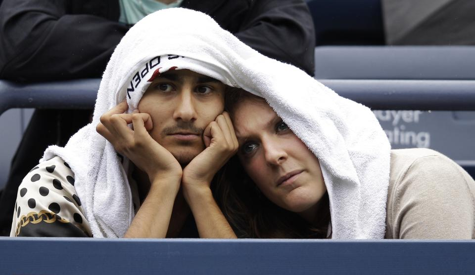 Roman Akbar and his girlfriend Sarah Yacob of Germany wait for play to resume at Grandstand Stadium during a rain delay at the U.S. Open tennis tournament in New York, Wednesday, Sept. 7, 2011. (AP Photo/Matt Slocum)