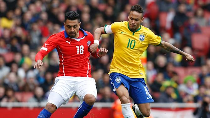 Brazilian striker Neymar challenges Chile's defender Gonzalo Jara (L), showing the steely determination that helped Brazil win the friendly match on March 29, 2015