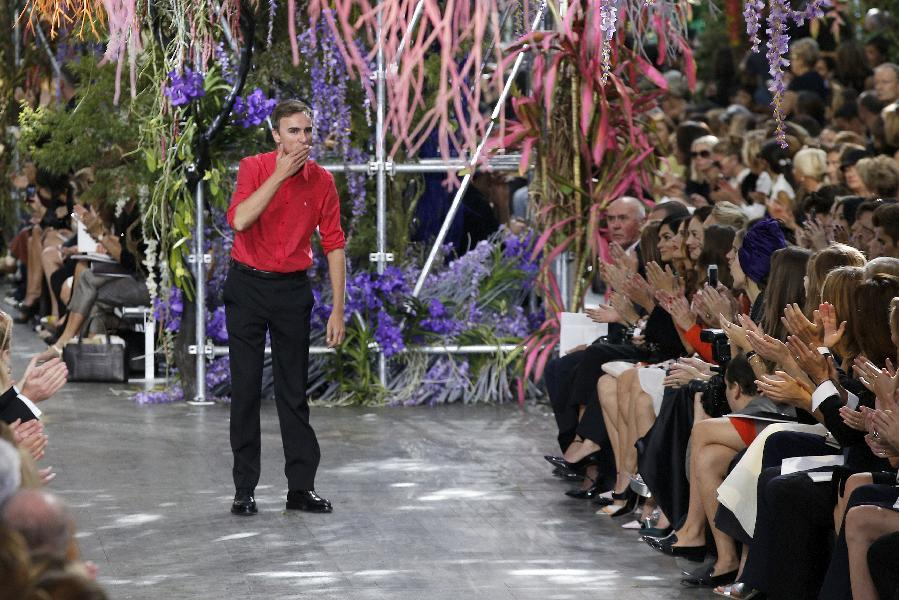 Belgian fashion designer Raf Simons blows a kiss to the audience as he acknowledges applause following the presentation of the ready-to-wear Spring/Summer 2014 fashion collection he designed for Christian Dior, Friday, Sept. 27, 2013 in Paris. (AP Photo/Christophe Ena)