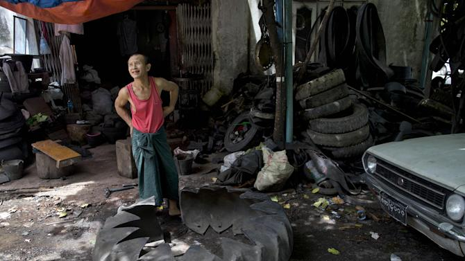 In this June 23, 2014 photo, a worker takes a break from cutting a worn-out tire to reuse as a buffer of a boat at a workshop that turn worn out tires in to flip-flops to buckets in suburbs of Yangon, Myanmar. Myanmar's tire recycling business unfazed by development and modernization, keep transforming old truck tires into rubber washers and bushes for motor cars, rice mills and other machine. (AP Photo/Gemunu Amarasinghe)
