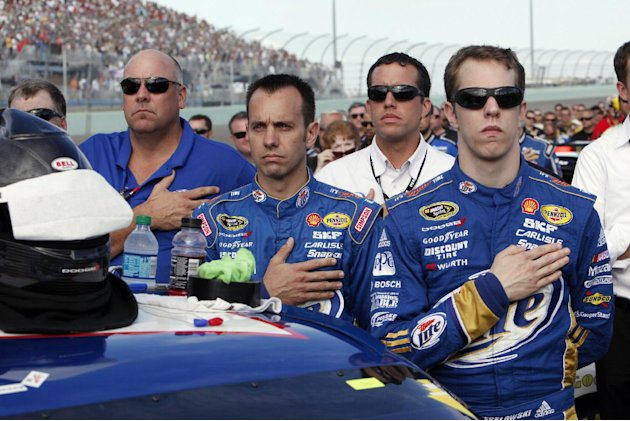 Brad Keselowski and members of his crew listen to the national anthem before the NASCAR Sprint Cup Series auto race at Homestead-Miami Speedway, Sunday, Nov. 18, 2012, in Homestead, Fla. (AP Photo/The