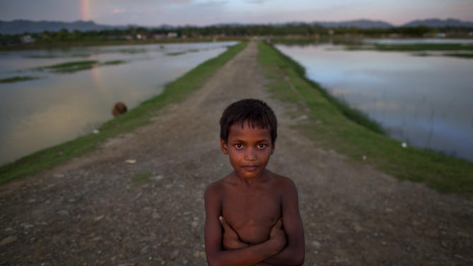 In this Sept. 11, 2013 photo, a Muslim boy stands close to a barbed wire fence on the border of Myanmar and Bangladesh in Maungdaw, Rakhine state, Myanmar. Children are the biggest victims of policies that for decades have systematically discriminated against Rohingya Muslims. With little or no food security, poverty-stricken families often put kids to work instead of sending them to school. (AP Photo/Gemunu Amarasinghe)