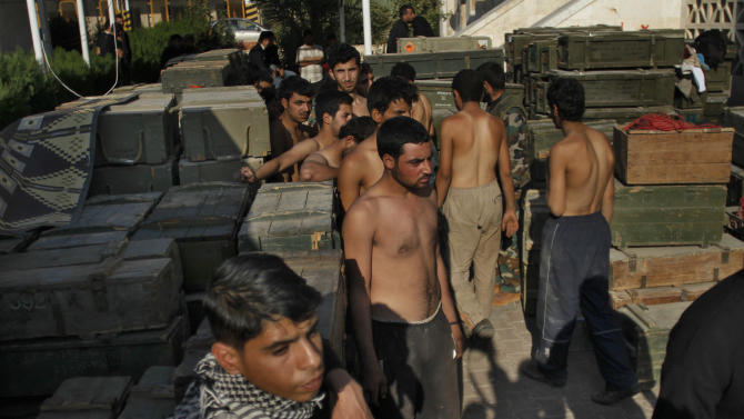 Syrian army soldier prisoners stand near ammunition after Syrian fighters took over the military base in Aleppo, Monday, Nov. 19, 2012. (AP Photo/ Khalil Hamra)