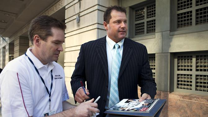 Roger Clemens, right, signs an autograph for baseball fan Dwayne Cantrell, as Clemens leaves federal court in Washington, Thursday, May 10, 2012. Clemens is on trial for allegedly lying to Congress in 2008. (AP Photo/Jacquelyn Martin)