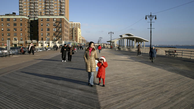 FILE - In this Dec.14, 2008, file photo Marina Katrova, and her 6-year-old daughter Masha walk on the wooden boardwalk that connects Brighton Beach, background, with Coney Island, in the Brooklyn borough of New York. A hearing is taking place in New York City Monday, March 12, 2012 on a planned makeover for stretches of the aging, 2.7-mile boardwalk that would include replacing it with a combination of plastic and concrete. (AP Photo/Dima Gavrysh, File)