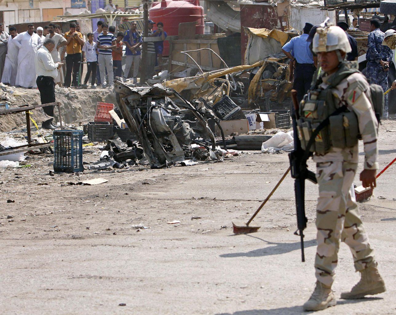 An Iraqi soldier stands guard as security forces inspect the scene of a car bomb attack in Basra, 340 miles (550 kilometers) southeast of Baghdad, Iraq, Sunday, Sept. 9, 2012. In violence, which struck at least 10 cities across the nation Insurgents killed at least 39 people in a wave of attacks against Iraqi security forces on Sunday, gunning down soldiers at an army post and bombing police recruits waiting in line to apply for jobs, officials said.