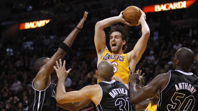 Los Angeles Lakers' Pau Gasol, center, looks to pass over Miami Heat's Chris Bosh, left, Shane Battier (31) and Joel Anthony (50) during the second half of an NBA basketball game on Thursday, Jan. 19, 2012, in Miami. The Heat defeated the Lakers 98-87. (AP Photo/Lynne Sladky)