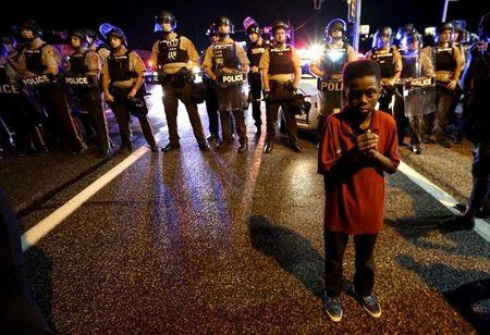 Amarion Allen, 11-years-old, stands in front of a police line shortly before shots were fired in a police-officer involved shooting in Ferguson