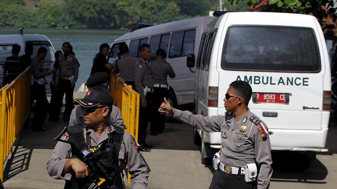 Indonesian policemen stand guard in front of ambulances at Wijayapura port near the prison island of Nusa Kambangan in Cilacap