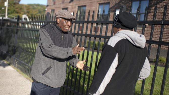 Liberian-American Moses Jensen, founder of the organization Immigrant Information Center, speaks to a resident in the Clifton neighborhood of Staten Island, New York