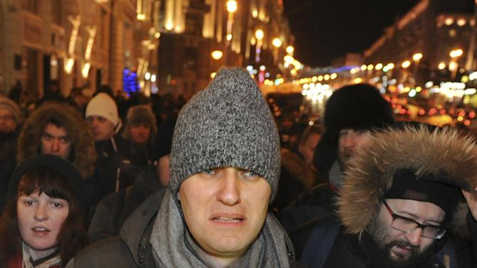 FILE - In this file photo taken on Wednesday, Dec. 31, 2014, Russian opposition activist and anti-corruption crusader Alexei Navalny, 38, surrounded by his supporters walks to attend a rally in Manezhnaya Square in Moscow, Russia. The opposition, usually all but invisible to the ordinary Russian, made a brief and small show two days before New Year's when a couple thousand demonstrators defied police to gather near the Kremlin in protest of the conviction of opposition stalwart Alexei Navalny and his brother on fraud charges.  (AP Photo/Anton Belitski, file)