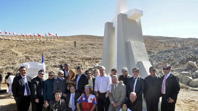 """In this photo released by Chile's Presidency, Chile's President Sebastian Pinera, center, poses for pictures surrounded by the miners who survived in entrapment longer than anyone else before, during an event marking the second anniversary of the cave-in at the San Jose mine in the Atacama in front of a monument on the outskirts of Copiapo, Chile, Sunday, Aug. 5, 2012. Pinera traveled to the northern city of Copiapo to join the men at the mouth of the mine that nearly became their rocky grave. They unveiled a five-meter (16 1/2-foot) cross as part of a monument known as the """"The 33 miners of Atacama: The miracle of life."""" (AP Photo/Chile's Presidency)"""