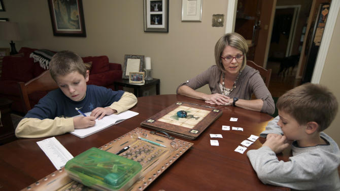 In this photo taken Sept. 15, 2011, Tiffany Hadden, center, helps her sons Cole, 9, left, and Connor, 6, with their homework in the Haddens' Little Rock, Ark., home. The two children are happy attending a Little Rock magnet school but the potential effect of a judge's ruling worries Mrs. Hadden. (AP Photo/Danny Johnston)