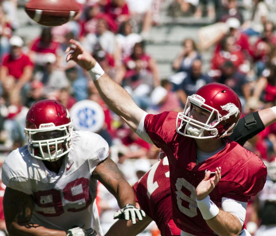 Arkansas quarterback Tyler Wilson (8) makes a pass as center Luke Carpenter, rear, tries to block tackle Lavunce Askew (99) during the second quarter of their spring NCAA college football game in Fayetteville, Ark., Saturday, April 21, 2012. (AP Photo/April L. Brown)
