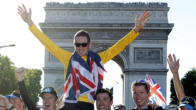 Sky Procycling rider and leader's yellow jersey Bradley Wiggins of Britain wears a British national flag as he celebrates with team mate his overall victory in front the Arc de Triomphe in Paris