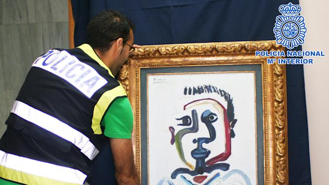 "In this photo released by the Spanish Police a police officer holds a forged Pablo Picasso oil painting in Sevilla, Spain, Saturday, July 7, 2012. The Interior Ministry says National Police have arrested four people for trying to sell a forged Pablo Picasso oil painting for up to 1.2 million euros ($1.5 million). The canvas, a counterfeit version of a 1964 work called ""The bust of Jeune Garcon"" was accompanied by false authenticity documents bearing the signatures of Paloma, one of the Spanish painter's daughters, and a renowned French art expert. (AP Photo/Spanish Police)"