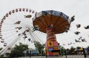 FILE - In this June 13, 2012 photo, visitors ride on the Ferris Wheel and Wave Swinger at Chicago&#039;s nearly century-old Navy Pier. Clinton Shepherd, park operations manager at the Navy Pier, rode the tourist spots Ferris wheel for more than 2 days over the weekend of May 18-19, 2013, bringing the world record for the longest ride to the birthplace of the amusement park favorite. (AP Photo/Charles Rex Arbogast, File)