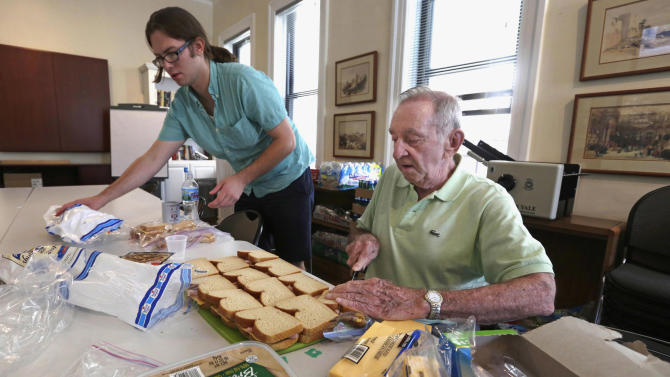"In this Aug. 1, 2013 photo, 85-year-old Don Tenbrunsel, right, and Alex Wissman, soup kitchen volunteers, work at making lunches at St. Josaphat's Church in Chicago. Tenbrunsel is a ""super ager,"" participating in a Northwestern University study of people in their 80s and 90s with astounding memories. So far the research has found scientific evidence that brains in this elite group resemble those of people decades younger. (AP Photo/M. Spencer Green)"