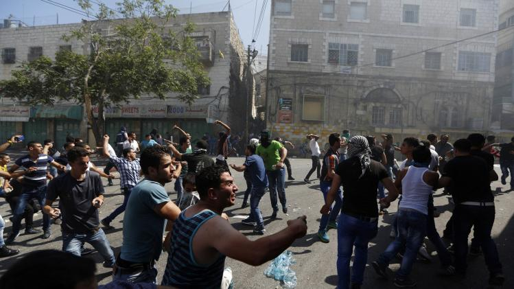 Palestinian protesters hurl stones toward Palestinian riot police trying to stop the protesters from clashing with Israeli troops, during a protest against the Israeli offensive in Gaza, in the West Bank city of Hebron