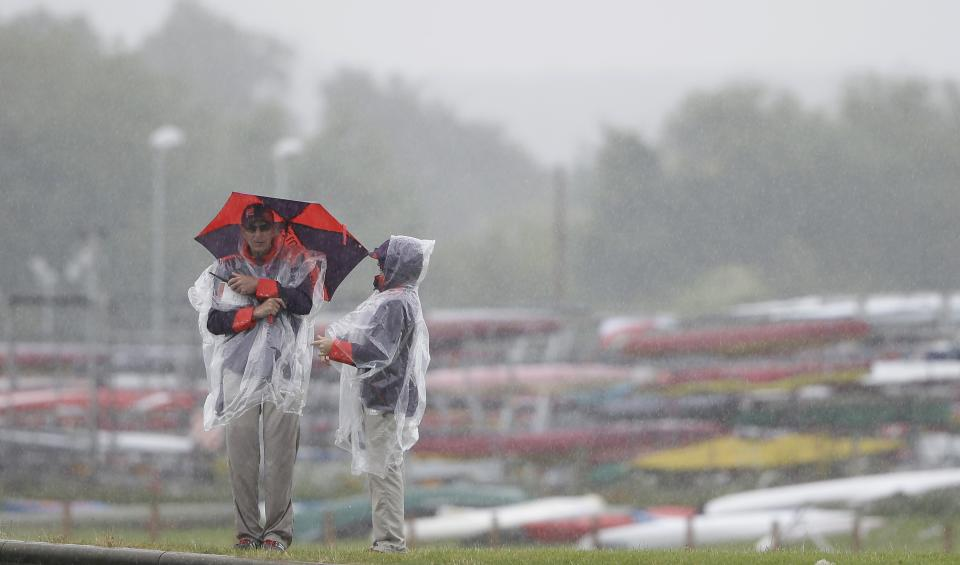 Two venue workers stand in the rain at the rowing venue in Eton Dorney, near Windsor, England, at the 2012 Summer Olympics, Saturday, Aug. 4, 2012. (AP Photo/Kirsty Wigglesworth)