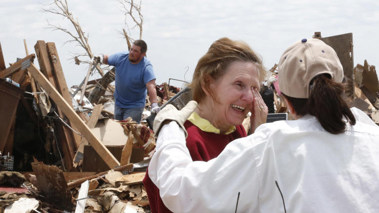 Christine Jones, center, is comforted by her cousin, Ann Worden, right, as she both smiles and wipes away the tears as she talks about looking for lost wedding rings at her tornado demolished home in Moore, Okla., Thursday, May 23, 2013. At left is Matthew Trawick, who is helping look through the rubble. (AP Photo/Sue Ogrocki)