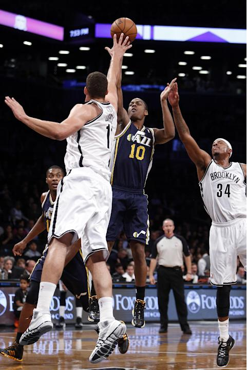 Utah Jazz's Alec Burks (10) shoots against Brooklyn Nets' Brook Lopez, left, and Paul Pierce (34) during an NBA basketball game Tuesday, Nov. 5, 2013, in New York. Brooklyn defeated Utah 104-88