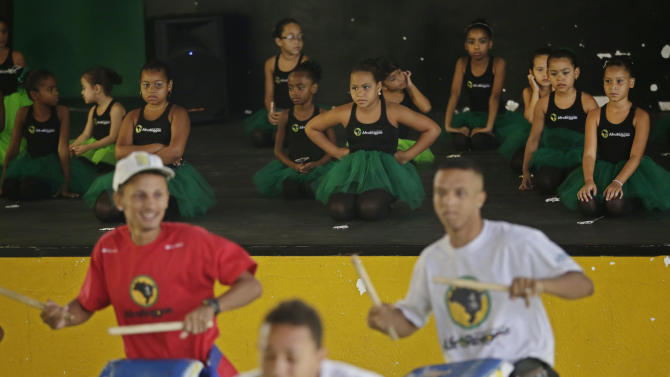 Young dancers watch drum players during a presentation before members of London's Royal Opera House in Vigario Geral slum of Rio de Janeiro, Brazil, Saturday, March 2, 2013. This past week Royal Ballet dancers shared their knowledge and advice with promising artists during an education symposium between the company and the cultural arts center Afro Reggae. (AP Photo/Silvia Izquierdo)