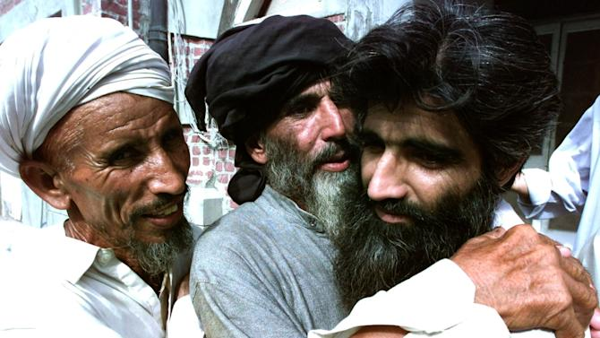 FILE - In this Wednesday, July 31, 2002, Taliban supporter Muhammad Jaffer, right, is received by his unidentified relatives after his release from the Kot Lakhpat Jail in Lahore, Pakistan. The Pakistani Taliban and the army have exchanged prisoners as a confidence building measure ahead of possible peace talks. Two Pakistani intelligence officials and a Taliban commander say the exchange Wednesday included six militants and two paramilitary Frontier Corps soldiers. (AP Photo/K.M Chaudary, File)