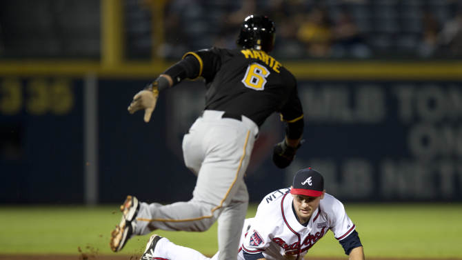 Pittsburgh Pirates' Starling Marte (6) steals second base as Atlanta Braves second baseman Phil Gosselin (15) dives for the wild throw in the fourth inning of a baseball game Tuesday, Sept. 23, 2014, in Atlanta. A run scored on the play. Pittsburgh won 3-2 and clinched a playoff berth. (AP Photo/John Bazemore)