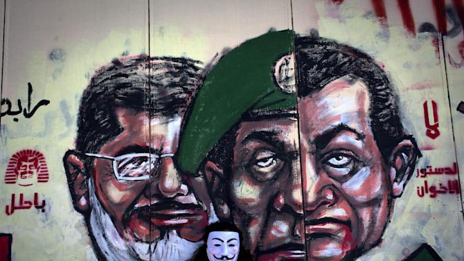 """FILE - In this Dec. 8, 2012 file photo, an Egyptian protester wears a Guy Fawkes mask while posing for a photo next to a mural painted overnight on the exterior wall of the presidential palace depicting president Mohammed Morsi, left, former military council ruler Hussein Tantawi, center and ousted President Mubarak with Arabic that reads """"No, the brotherhood's constitution is not valid, in Cairo. Egyptian authorities switched the venue for the trial of the former Islamist president on Sunday, Nov. 3, 2013 a last-minute change made after the Muslim Brotherhood called for mass demonstrations at the original location. The trial of Morsi, now to be held east of the capital on Monday, could lead to another round of bloodshed as his supporters look likely to face an emboldened security apparatus that has boosted its forces for the hearing.(AP Photo/Nasser Nasser, File)"""