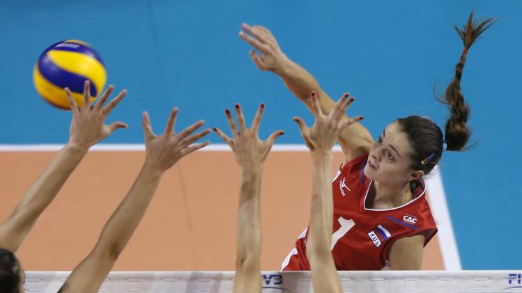 Yana Shcherban of Russia spikes the ball against Naz Aydemir Akyol and Kubra Akman of Turkey during their FIVB Women's Volleyball World Grand Prix 2014 final round match in Tokyo