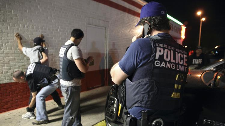 Federal agents with ICE detain a man