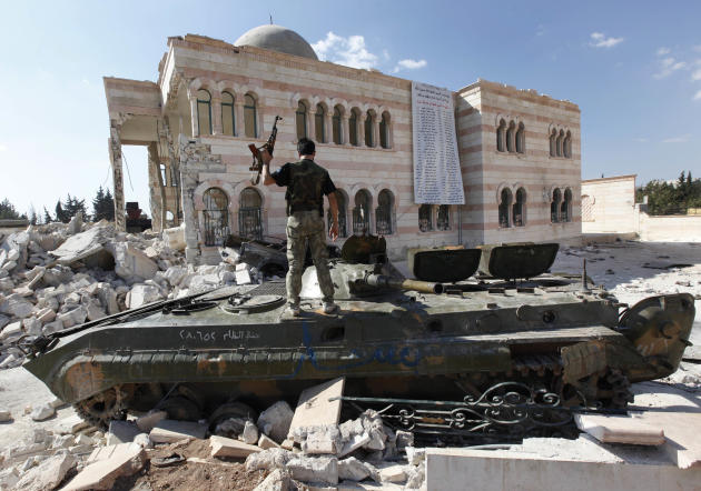 A Free Syrian Army soldier stands on a damaged Syrian military tank in front of a damaged mosque, which were both destroyed during fighting with government forces, in the Syrian town of Azaz, on the o