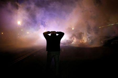 File photo of a protester with his hands on his head as a cloud of tear gas approaches after a grand jury returned no indictment in the shooting of Michael Brown in Ferguson, Missouri