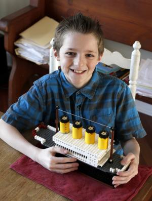 This March 9, 2012 photo shows John Marcus Payne with his Lego model of the Titanic cruise ship in Glencoe, Ill. Payne has been a student of the Titanic since kindergarten. He has scrupulously researched the ship, built a model out of Lego freehand and successfully lobbied his fifth-grade teacher in suburban Chicago to let him mark the disaster's centennial with a multimedia presentation for his class. (AP Photo/Charles Rex Arbogast)
