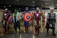 Participants wearing super heroes costumes walk in line during the 14th Ani-Com and Games exhibition in Hong Kong. One of Asia's biggest animation and comic fairs opened Friday in Hong Kong, attracting thousands of fans and bringing some fun back into super heroes after the Batman movie shootings in Colorado. AFP PHOTO / Philippe Lopez