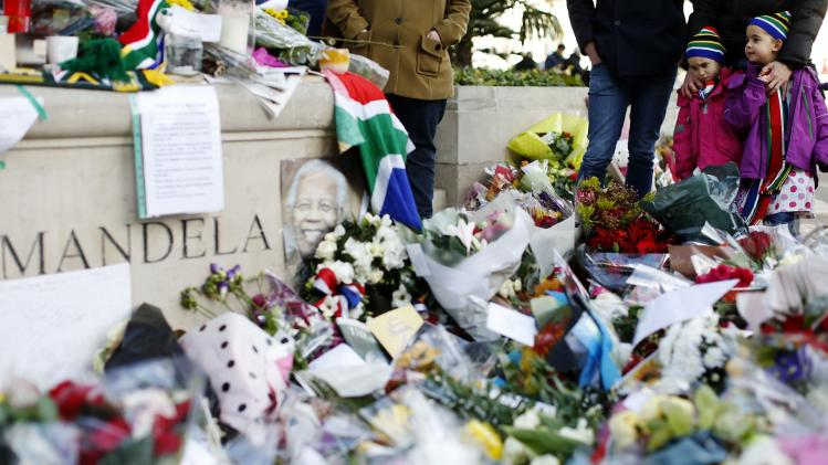 The statue of former South African President Nelson Mandela is surrounded by flowers in Parliament Square in central London