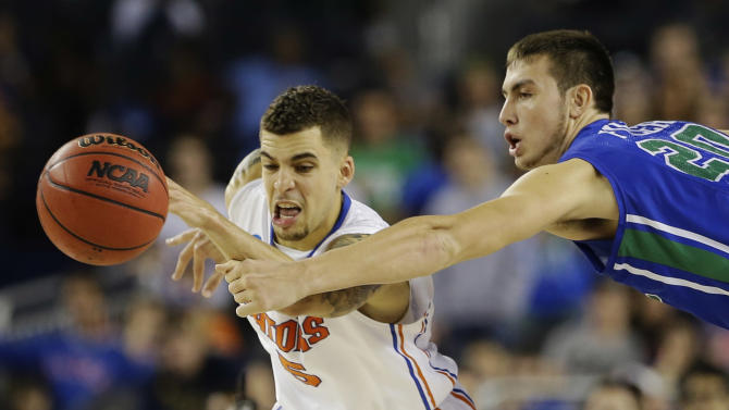 Florida's Scottie Wilbekin (5) and Florida Gulf Coast's Chase Fieler (20) go after a loose ball during the second half of a regional semifinal game in the NCAA college basketball tournament, Saturday, March 30, 2013, in Arlington, Texas. (AP Photo/Tony Gutierrez)