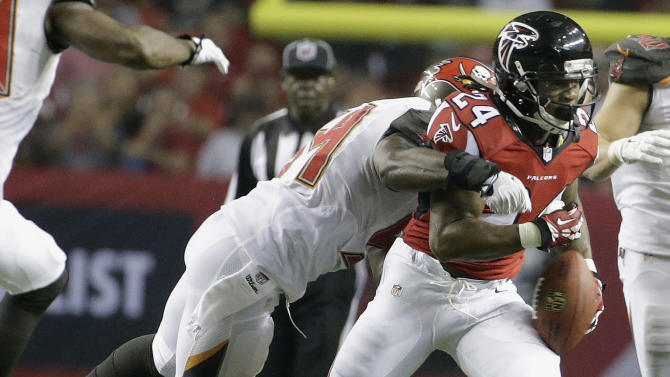 Tampa Bay Buccaneers outside linebacker Lavonte David (54) strips the ball from Atlanta Falcons running back Devonta Freeman (24) during the second half of an NFL football game, Thursday, Sept. 18, 2014, in Atlanta. (AP Photo/David Goldman)
