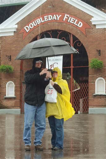 Andy, left, and Nancy LaPorta of Latham, N.Y., pose for a photo in front of a closed Doubleday Field in Cooperstown, N.Y., after the Baseball Hall of Fame Classic was canceled due to rain, Saturday, M