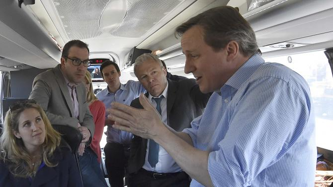 Britain's Prime Minister David Cameron speaks with journalists on the Conservative Party 'battle bus' whilst campaigning  in northern England