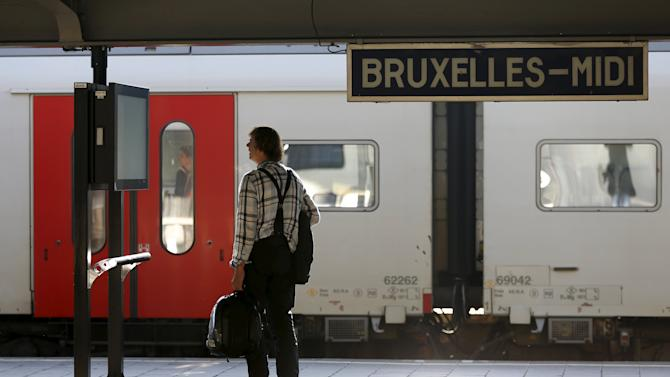 A stranded passenger checks an information board on an empty platform during a strike at Midi/Zuid railway station in Brussels