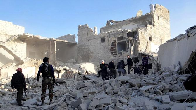 Citizen journalism image provided by Aleppo Media Center AMC which has been authenticated based on its contents and other AP reporting, shows Syrian rebels stand in the rubble of damaged buildings due to government airstrikes, in the neighborhood of Karam Tarab near Aleppo International Airport, in Aleppo, Syria, Wednesday, Feb. 13, 2013. Syrian rebels fought pitched battles Wednesday against regime forces at a military base that protects a major airport in the country's north in fighting that has left more than 40 government troops dead, opposition activists said. (AP Photo/Aleppo Media Center AMC)