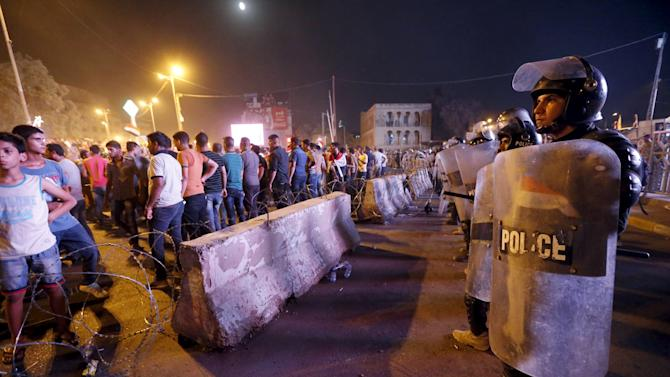Riot policemen stand in front of protesters during a demonstration against the poor quality of basic services, power outages and calling for trial of corrupt politicians in Baghdad