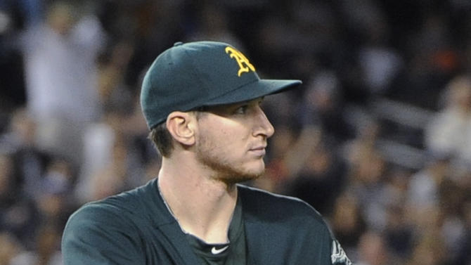 Oakland Athletics starting pitcher Jarrod Parker reaches under his jersey to retrieve the baseball after he caught a ground ball by New York Yankees' Ichiro Suzuki during the third inning of a baseball game Friday, Sept. 21, 2012, at Yankee Stadium in New York. Suzuki singled on the play. (AP Photo/Kathy Kmonicek)