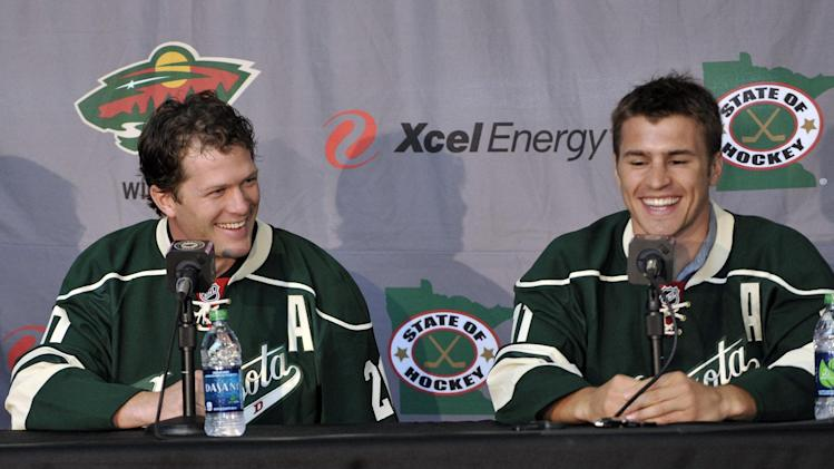 New Minnesota Wild NHL hockey players Ryan Suter, left, and Zach Parise are introduced during a news conference Monday, July 9, 2012 in St. Paul, Minn. The two signed 13-year contracts with the Wild for $98 million. (AP Photo/Jim Mone)