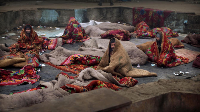 In this photo taken on Jan. 19, 2012, Indian squatters sit together in rented blankets after waking up next to Park No. 2 near Jama Masjid in New Delhi, India. For thousands of people struggling at the bottom of India's working class, the Meena Bazaar parking lot and the handful of places like it scattered across New Delhi are cheap refuges in a city where many migrants can't even afford to rent slum shanties. (AP Photo/Kevin Frayer)