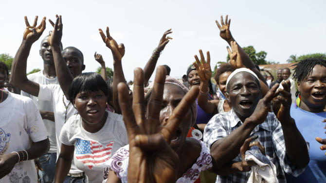 Supporters of incumbent President Ernest Bai Koroma cheer and hold up four fingers to show they want the ruling party to sweep the elections, as Koroma leaves after voting, in Freetown, Sierra Leone, Saturday, Nov. 17, 2012. A decade after Sierra Leone's brutal civil war, voters on Saturday chose between an incumbent president who has provided new roads and free health care and a field of opposition candidates who decry the poverty and pace of economic recovery.(AP Photo/Rebecca Blackwell)