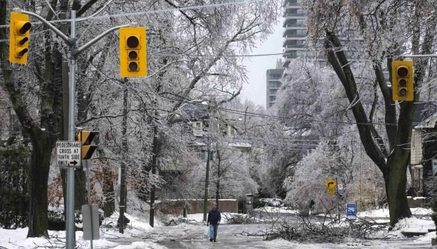 A man walks down the street behind traffic lights with no power following an ice storm in Toronto