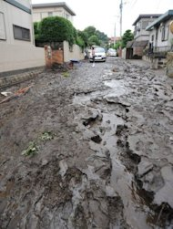 A road is covered in mud in a residential area after heavy rain fell at Kumamoto city on Japan's southern island of Kyushu. At least 17 people died, 20 were missing and 50,000 were ordered to evacuate as the heaviest rainfall on record pounded Kyushu, officials and reports said Thursday